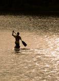 canoeing dans le coucher du soleil Images stock