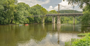 Canoeing on the James River. Botetourt County, VA – August 12th: Canoeing on the James River going under a hanging bridge located in Buchanan, Botetourt royalty free stock photos