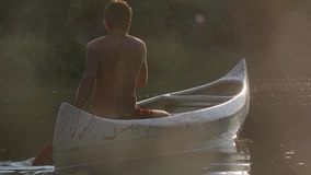 Canoeing on a lake. Canoeing in beautiful natural environment in sunset light stock video