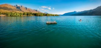 Canoeing on Lake Wakatipu at Glenorchy, NZ. One person canoeing at lake Wakatipu close to Glenorchy Wharf close to sunset. Glenorchy is a charming alpine village Royalty Free Stock Photo
