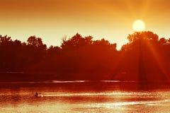 Canoeing mensensilhouet op een meer Stock Foto's