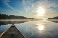 Canoeing on a misty summer morning on Corry Lake. Royalty Free Stock Image
