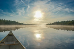 Canoeing on a misty summer morning on Corry Lake. Stock Images