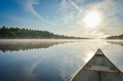 Canoeing on a misty summer morning on Corry Lake. Stock Photos