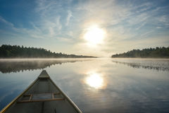 Canoeing on a misty summer morning on Corry Lake. Stock Image