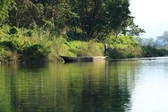 Canoeing Safari des Mannes auf hölzernen Boot Pirogues auf dem Rapti-Fluss, in Nationalpark Chitwan, Nepal lizenzfreie stockfotografie