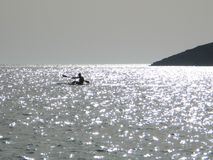 Canoeing in the Sea. The silhouette of a man canoeing in the sea royalty free stock images