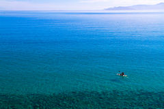 Canoeing on serene sea waters. Royalty Free Stock Photo