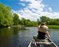 Canoeing on a small river. Young woman paddling on a gentle little river royalty free stock image