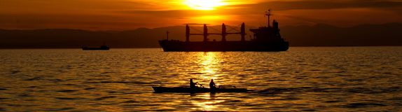 Canoeing in the sunset. A picture of two people canoeing in the sea,and a ship in the background,in a sunset day afternoon,in a town in Greece,Thessaloniki Royalty Free Stock Photography