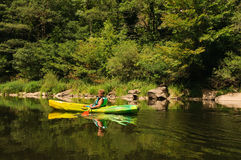 Canoeing van de jongen op rivier Stock Afbeeldingen