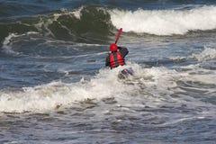 Canoeing van de mens in golven stock afbeelding