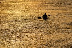 Canoeist out in beautiful golden sunrise stock photo