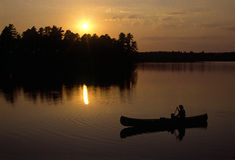 Canoeist at sunset in silhouette Royalty Free Stock Images