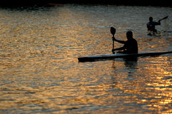 Canoeists paddling on lake Stock Images