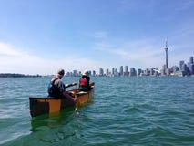 Canoers, das vor den Toronto-Skylinen schaufelt Lizenzfreies Stockfoto