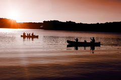 Canoers on the lake with setting sun Royalty Free Stock Image