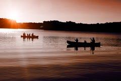 Canoers op het meer met het plaatsen van zon Royalty-vrije Stock Afbeelding