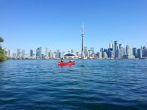 Canoers paddling in front of the Toronto skyline. Two women paddle a red canoe in front of the Toronto skyline in Lake Ontario. The Toronto Islands, about 1.4 km Royalty Free Stock Photos
