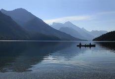 Canoers retroiluminado en el parque provincial de Waterton del lago mountain Imagen de archivo
