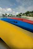 Canoes. Three different colored canoes turned over on a beach near the water Stock Images