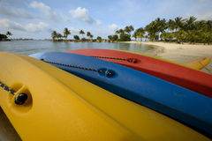 Canoes. Three different colored canoes turned over on a beach near the water Stock Photo