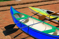 Canoes. A closeup of two colourful canoes on a brick pavement Royalty Free Stock Images