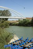 Canoes anchored at harbour in green river with the bridge in the background. Maremma, Tuscany, Italy