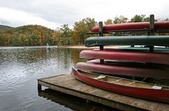 Canoes on a Boat Dock. Red and green canoes on a canoe rack next to a boat dock in a lake, with autumn foliage in background royalty free stock image
