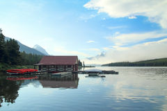 Canoes and Boathouse on a Lake. Canoes and Boathouse at Dawn - Maligne Lake, Jasper National Park, Alberta, Canada Royalty Free Stock Photography