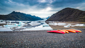 Canoes at cold glacial lake in the mountains, Iceland Royalty Free Stock Images