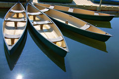 Canoes in Dock. Four canoes docked in a circular fashion along the dock with the deep blue waters Royalty Free Stock Photos