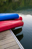 Canoes on a dock next to a lake. Three canoes on a dock next to a lake in Asturias, Spain Royalty Free Stock Photos