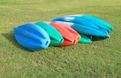 Canoes on green grass field Stock Photos