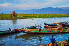 Canoes on Inle Lake, Myanmar. YWAMA, MYANMAR - FEBRUARY 18, 2018: Numerous canoes with boaters in wharf of Nga Phe Chaung Monastery of jumping cats, located on Royalty Free Stock Photo