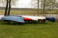 Canoes jacked riverside. A number of canoes and rowboats standing in a row on a meadow and jacked by the river Stock Photos
