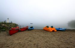 Canoes and kayak in fog stock photos