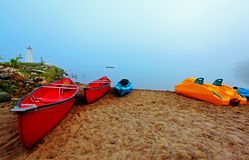 Canoes and kayaks  at sunrise. Canoes and kayaks in early morning light Royalty Free Stock Photos