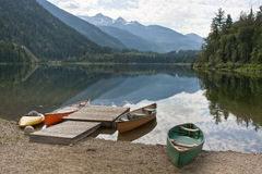 Canoes at a lake. Some canoes ly on the shore of a quiet lake in the rocky mountains Stock Photography