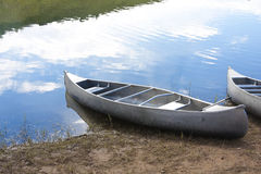 Canoes on the Lake. A couple of canoes resting on the lake shore. Lots of copy space royalty free stock photos