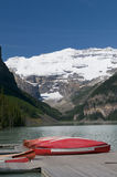 Canoes at Lake Louise. With Victoria glacier in the background Stock Images