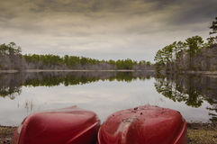 Canoes by lake side and reflection Royalty Free Stock Photo