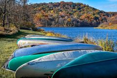 Canoes lined up by Devils Lake. A row of canoes lined up along the shoreline of Devils Lake State Park in Baraboo, Wisconsin in the fall stock images