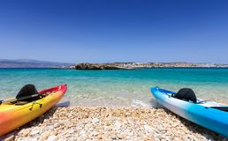 Canoes lying on a pebble beach in the Cyclades Royalty Free Stock Photos