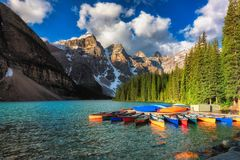 Canoes on Moraine lake, Banff national park in the Rocky Mountains, Alberta, Canada. Beautiful turquoise waters of the Moraine Lake with snow-covered peaks Royalty Free Stock Images