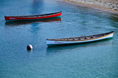 Canoes in Nantucket. Two canoes, the Cassie and Grace are tied down on Nantucket Island, MA Royalty Free Stock Image