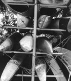 Canoes, out of use. A rack of canoes laying unused and stacked up for the winter. Produced in grainy black and white to emphasise that 'end of summer' feeling Royalty Free Stock Photo