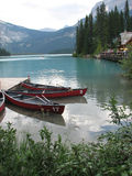 Canoes on picturesque lake. Scenic view of canoes on picturesque lake with trees and mountainous background Royalty Free Stock Images