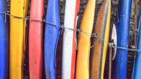Canoes. Red, blue, yellow, white canoes in a row standing against the wall stock image