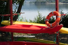 Canoes. Red and Yellow canoes on the shore of a lake stock images